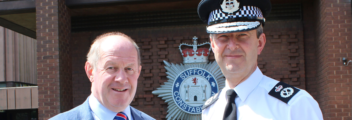Chief and PCC outside police HQ in front of Constabulary crest