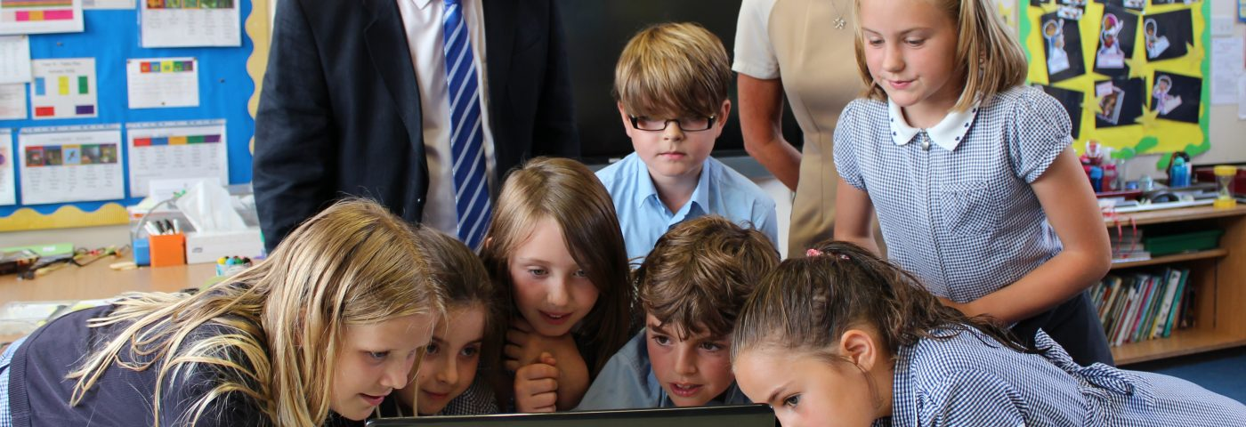PCC and a group of young pupils looking at a laptop